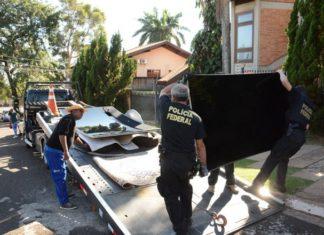Policiais carregam bens apreendidos em residência de um dos investigados – Foto: Bruno Henrique