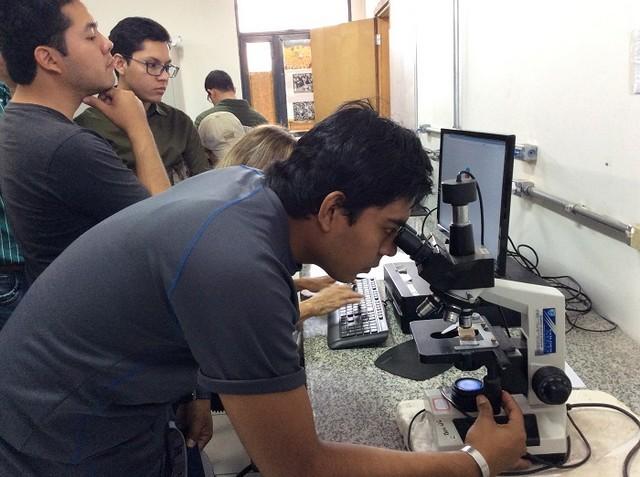 Estudante da Bolívia utiliza microscópio durante a visita – Foto: Ana Maio